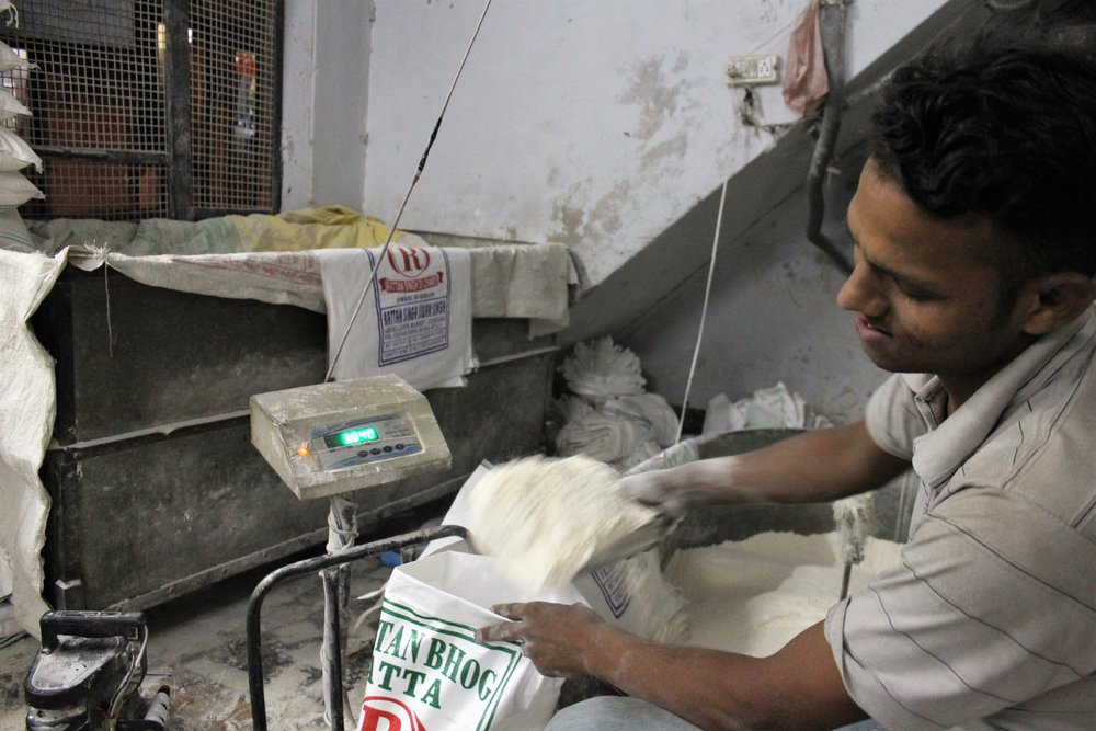 A migrant worker at a flour mill in Ludhiana packs flour bags. Credit: Atul Anand