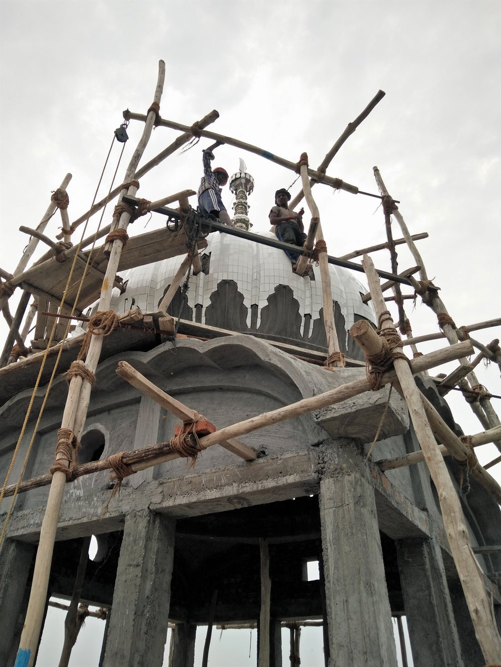 Migrant workers build Gurudwara dome. Credit: Ankur Jayaswal