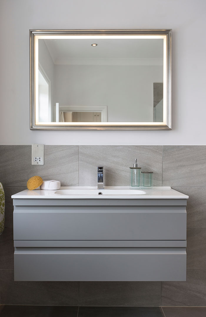 modern-bathroom-walls-lamp-white-wall-paint-marble-countertop-mounted-washbasin-alumunium-faucet-head-purple-flowers-on-glass-vase-mirror-with-frame-soap-plate-vanity-mirror-in-near-bath-tub.jpg