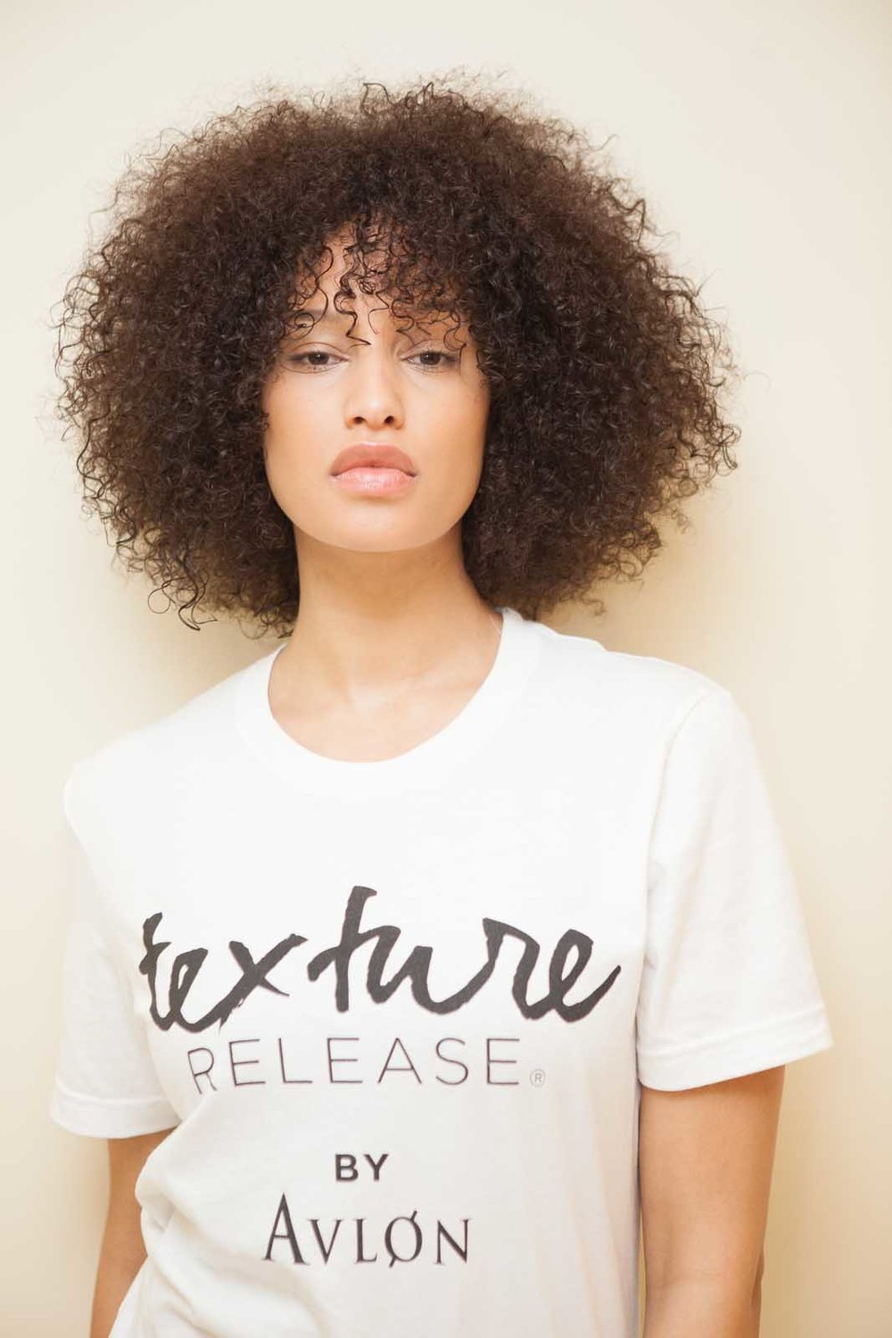 - The Texture Release™ Curl Shape & Shine Cream was worked through the hair root to tip to bolster texture and definition. For more volume, sections were wrapped round a curling wand and teased out to form a dramatic afro shape.