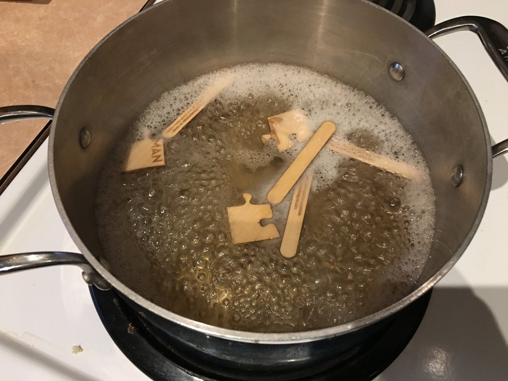 Boiling the popsicle sticks to ensure they were sterilized and ready for food contact.