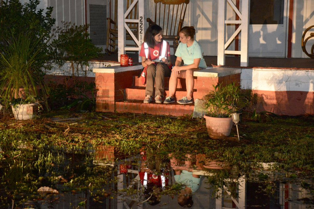 A Red Cross volunteer helps an individual whose house was flooded.