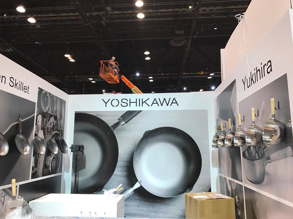 ヨシカワ社ブース。照明のセッティングスタッフ(後ろの重機に乗るスタッフ)待ちです。 回ってきたら照明の位置を確認・調整します。