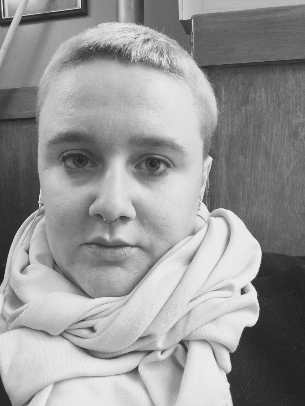 A black-and-white selfie of author, a white femme, wearing a voluminous light-colored scarf. She has short blonde hair and a septum ring.