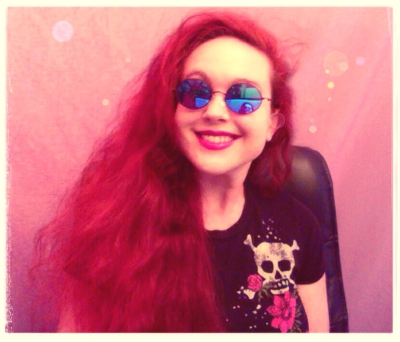 A person with long, very bright red hair smiles at the camera, wearing mirrored blue sunglasses and a black T-shirt with a white skull-and-crossbones and pink rose. The image is saturated with warm colors, except for the cool blue shades. (They're cool in both senses of the word.)