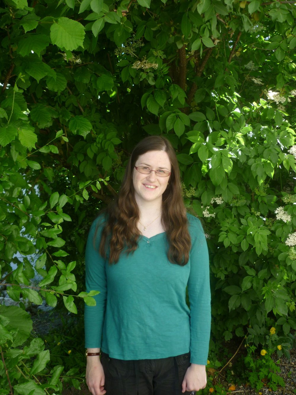 The image is portrait style. It shows the upper two-thirds of a woman in her twenties. She has her head tilted slightly to the right and is smiling. She has long wavy brown hair, pale skin, and wears glasses. Her hands are by her sides. She is wearing a dark green long-sleeved t-shirt and black trousers. She is standing in front of an elder bush and is surrounded by green leaves. Tree branches can be seen behind her, and to her right small white flowers are visible among the leaves.