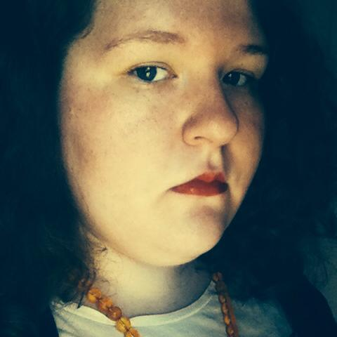 A close-up photo of a fat white woman's face. She is looking directly at the camera and is not smiling, and is wearing a white shirt and orange necklace.