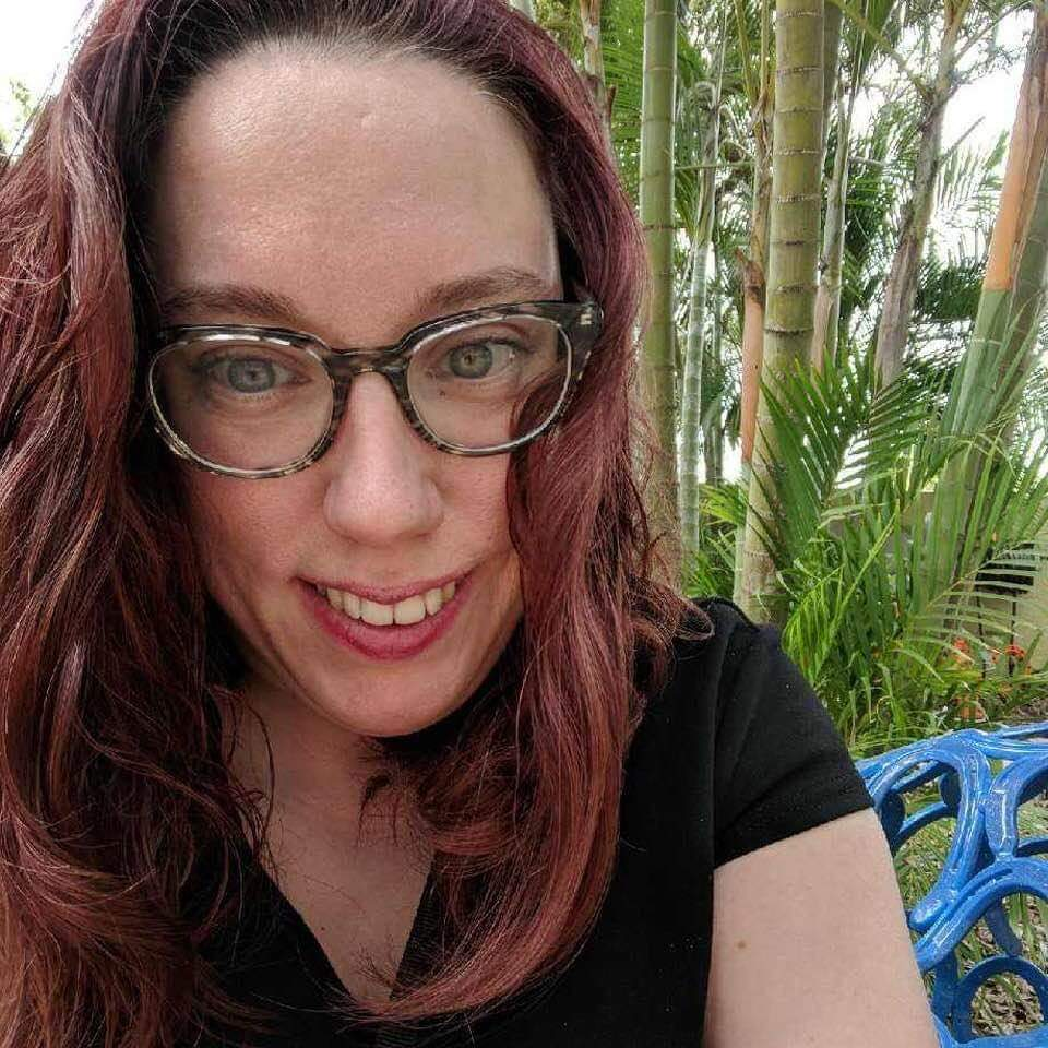 Author sits on a blue bench in front of some palm trees in Florida. The photo is cropped so you can only see part of her black shirt. She has reddish shoulder-length wavy hair, gray tortoise shell Warby Parker glasses and a toothy smile.