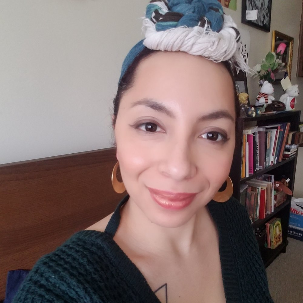 Image of a young woman smiling at the camera. She is wearing a blue and white headwrap, gold hoop earrings, and green sweater. She has light tan skin with dark red-brown hair peeking through the headscarf. Behind her is a black bookshelf that is lined up with an assortment of books and trinkets.