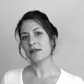 A black-and-white photograph of the author, who is staring into the camera, with a neutral expression. She is wearing a white t-shirt, and has her dark hair tied up.