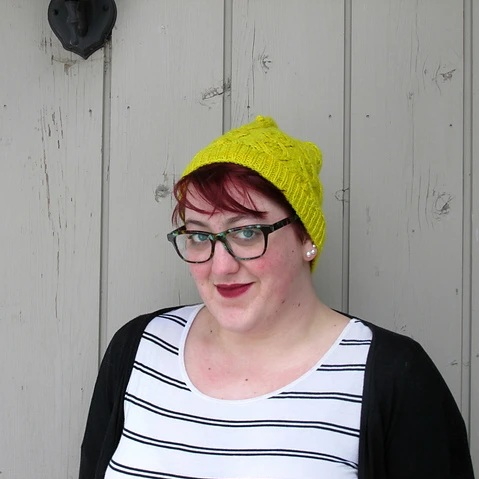 The photo shows the author from the chest up. She is standing in front of a grey wall at a three-quarter angle to the camera. Auburn bangs peek out from under a yellow knit hat, and she wears green tortoiseshell glasses. She has white skin, blue eyes, and her dark red lips are in a closed-mouth smile.