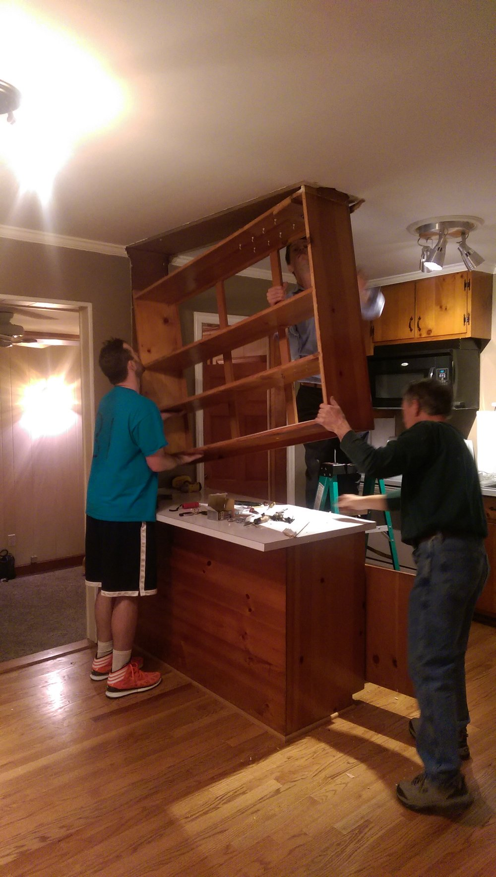 Look at my husband, brother-in-law and dad GO. There was literally a foot long bolt holding that thing to the ceiling.