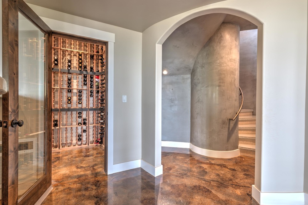 Spiral concrete staircase leads from great room to a secondary living room with wet bar, wine cellar, and butlers kitchen. French doors lead out to the covered patio and pool.