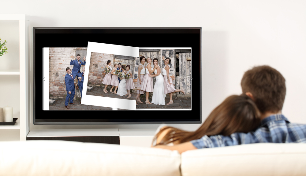 Sitting back relaxing, viewing their Wedding Album on a big screen TV.