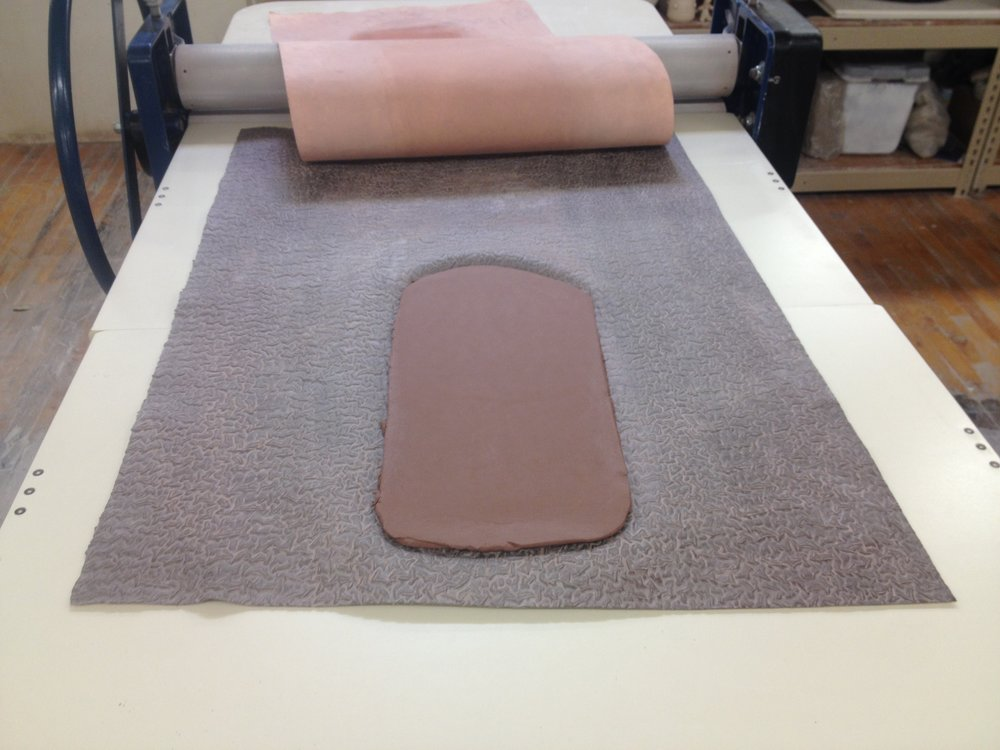 the next step is to place a 5lb block of clay onto a textured mat and running it through the slab roller.
