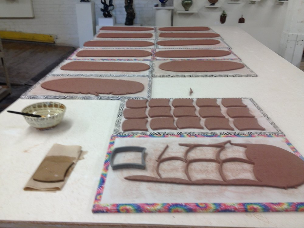 the tiles are cut from the slab using a hand held cutter and then transferred to another ware board. The tiles are sandwiched between two ware boards which keeps the tiles flat while allowing the moisture to escape.