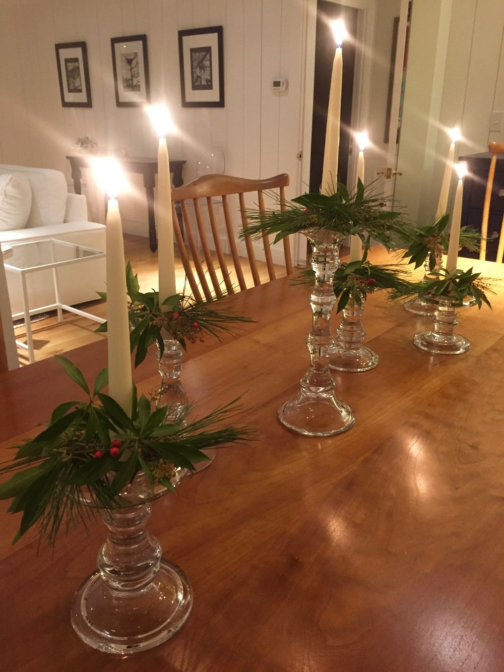 a large dining table was set with glass candles and live greens.
