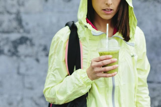 An athletic woman holding a glass of green juice. Photo Credit Dirima/iStock/Getty Images