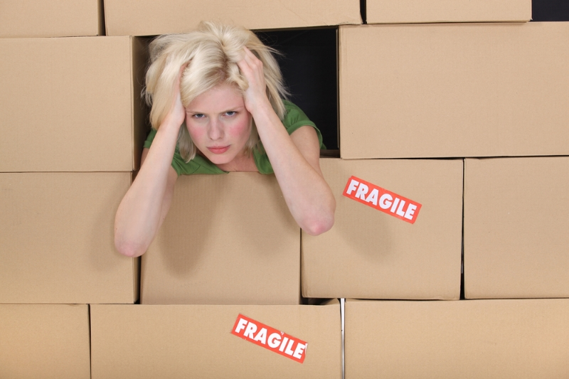 Moving day is stressful as evident by this woman with her hands on her head in between boxes