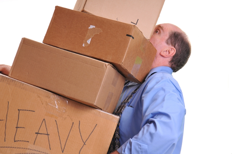 man moving too many heavy boxes