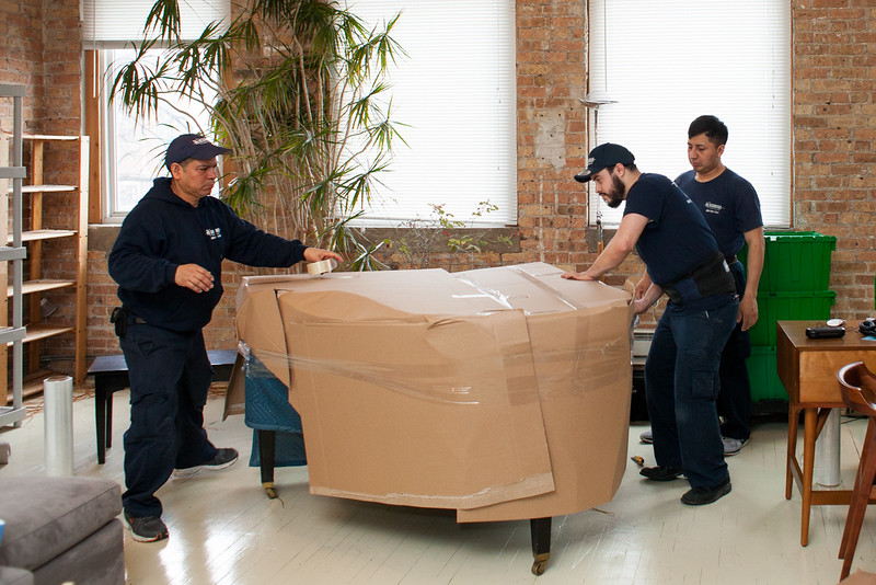 professional packers packing a piano