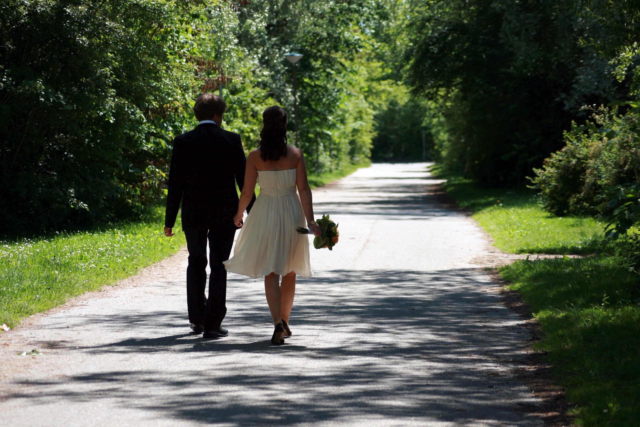 Married couple walking down country road.