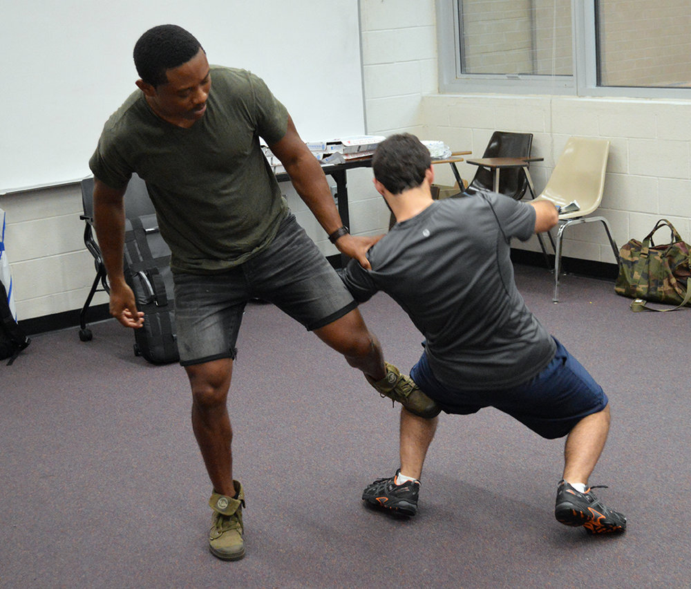 Instructor Pandit Mami, left, demonstrates a self-defense strategy on UCF student Alex Lantz, right, at the Krav Maga session in UCF's Engineering I building on Wednesday, Sept. 14, 2016. The one-hour session, hosted by Knights for Israel, taught UCF students the Israeli form of self-defense, which combines boxing, wrestling and other fight training.