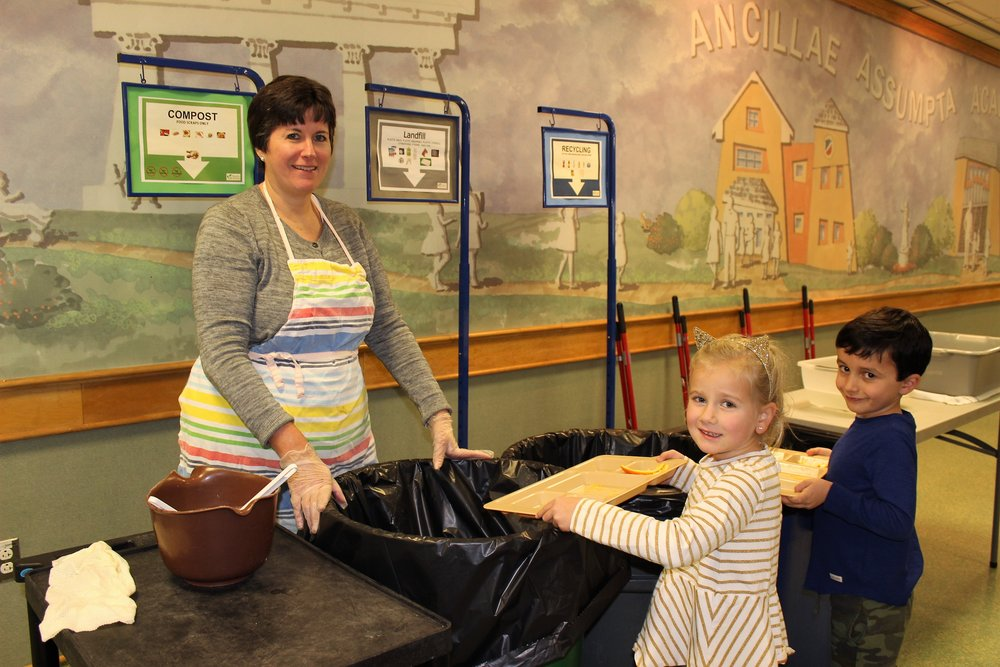 Mrs. Handel and Kindergartners, Ryan (left) and Charlie (right), compost in Ancillae-Assumpta's student dining hall.