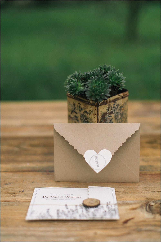 Briefumschlag braun mit Herzaufkleber und Paarlogo