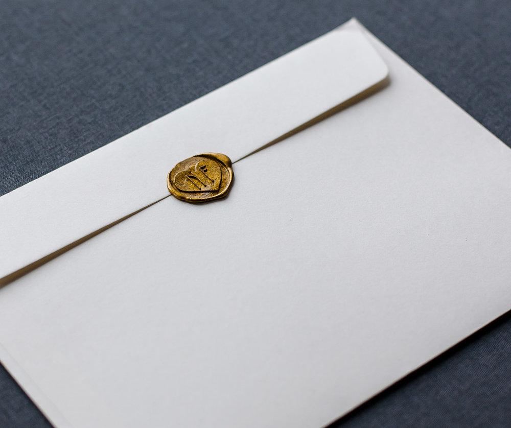 Weißer Briefumschlag mit Siegelstempel Gold