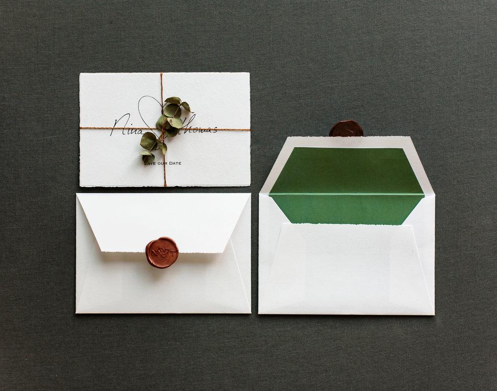 Save the Date Karte mit Kupferkordel und weißer Briefumschlag mit grünem Innenfutter und Kupfer Siegelstempel