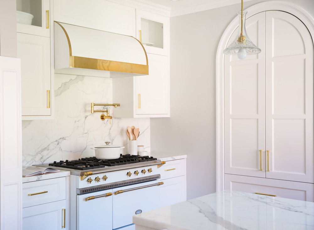 white lacanche stove gold hardware kitchen carrera marble counter backsplash danish scandinavian pantry hood
