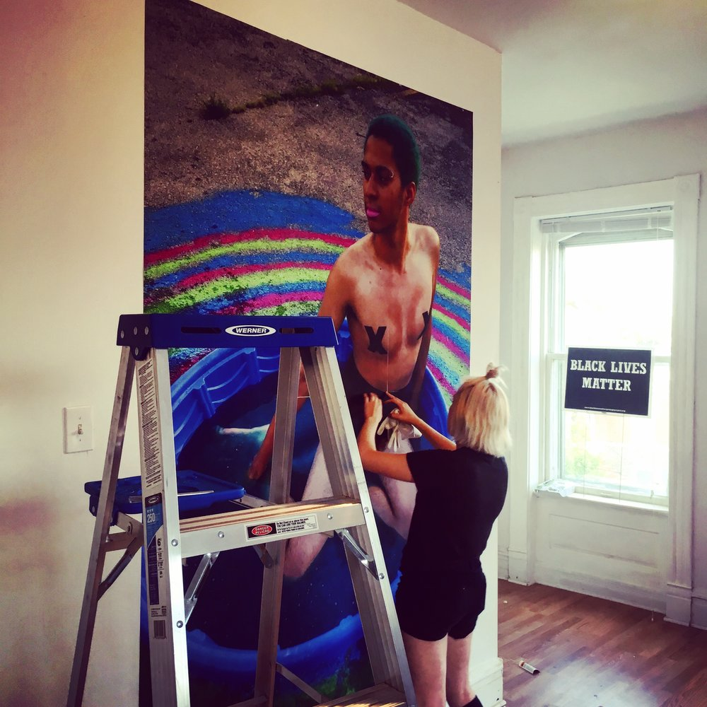 """Holly McGraw installing work for the """"Hard Times Art Show"""""""