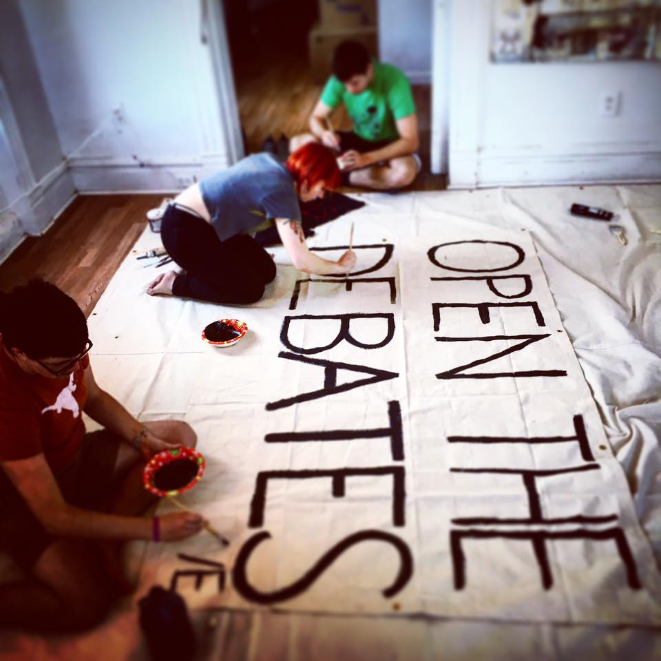 making banners for the protests at the St. Louis presidential debate