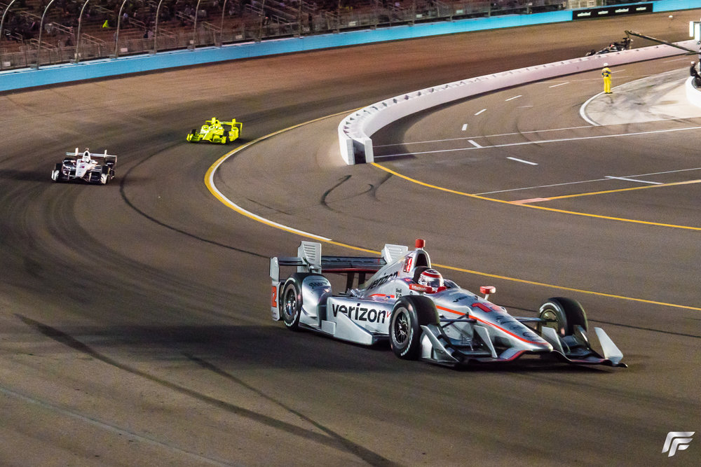 Will Power leads under the lights with Helio Castroneves and Simon Pagenaud pursuing.