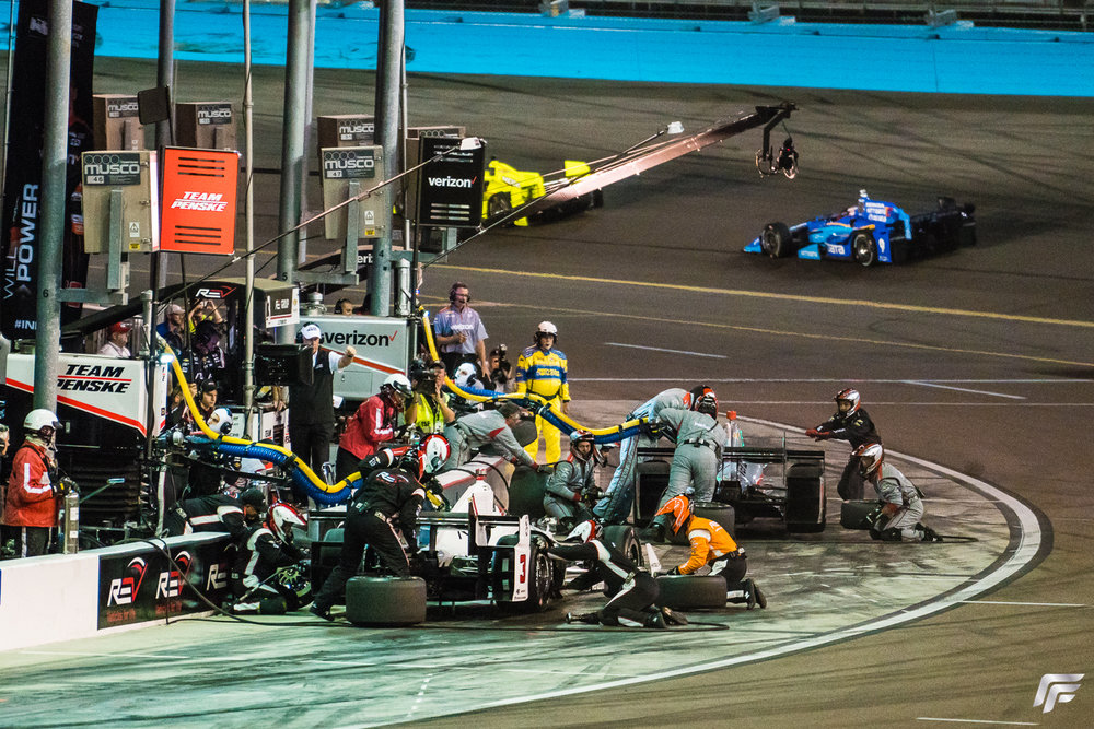 Simon Pagenaud's brightly colored Menards Honda can be seen in the distance remaining on course while Castoneves and Power are in the pits.