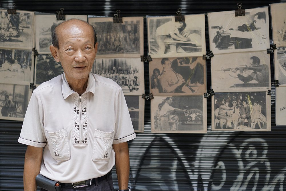 A man sells photos of his beloved King Rama IX on the streets of Bangkok, Thailand.