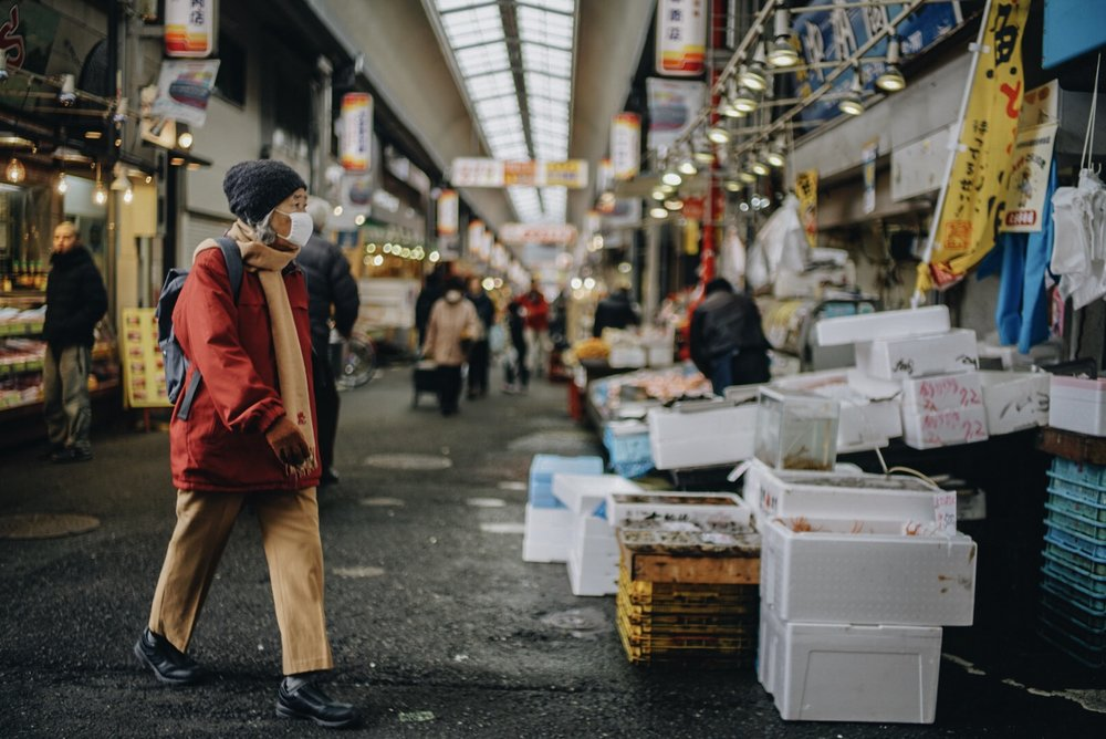 A woman walks through a street market on a cold morning in Kobe, Japan.