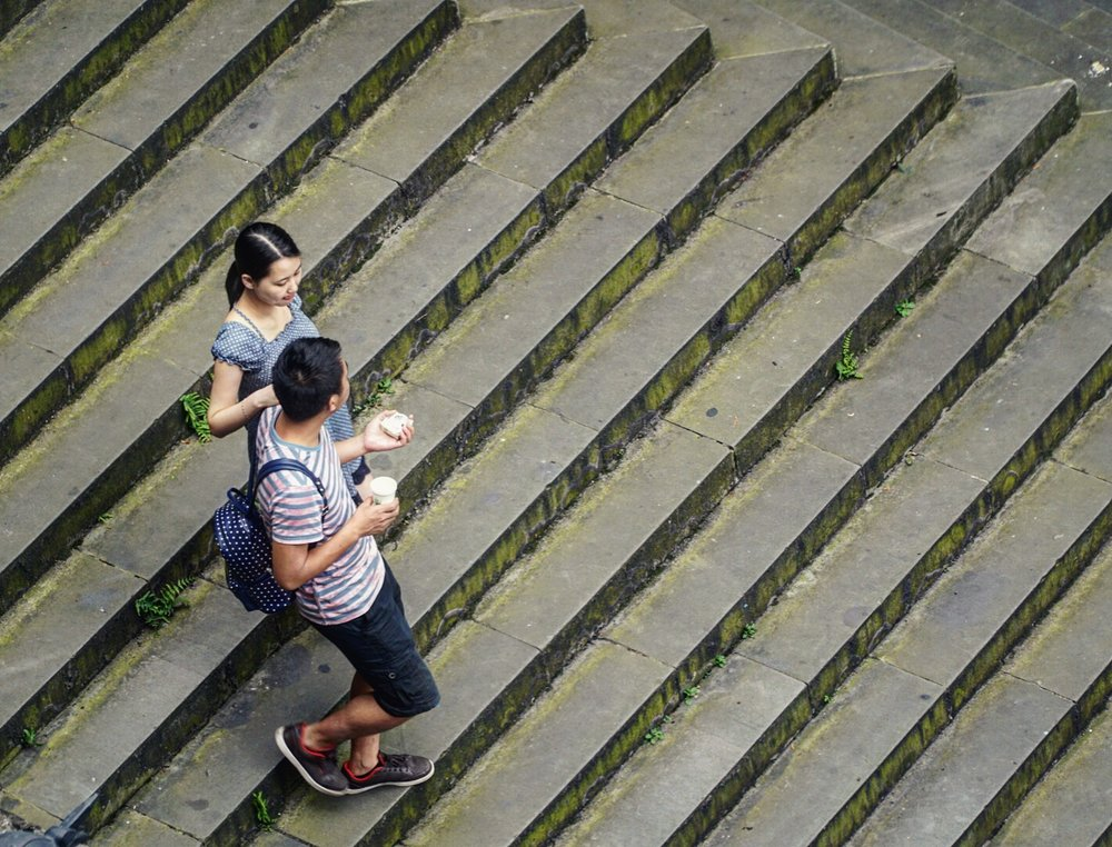 A young couple navigates a staircase. Chongqing, China.
