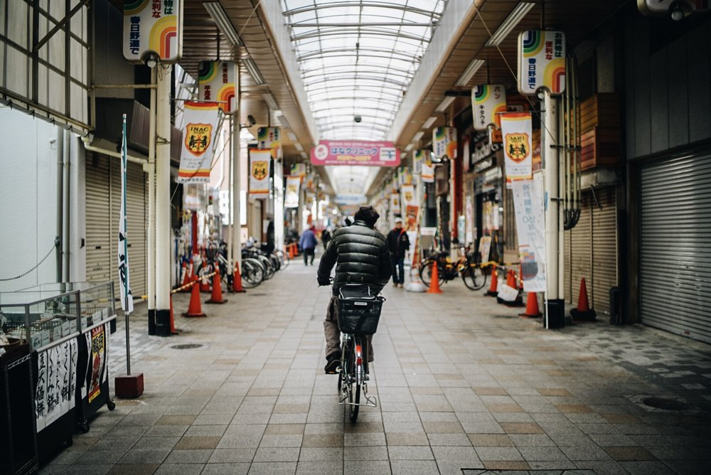 A man rides his bike through a quiet market in Kobe, Japan.