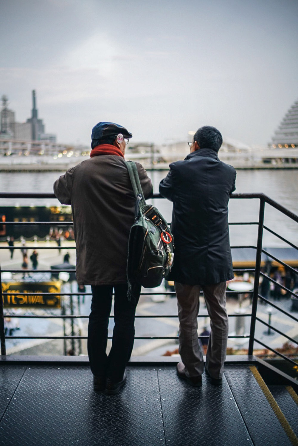 Two men chat while enjoying the view of the bay. Kobe, Japan.