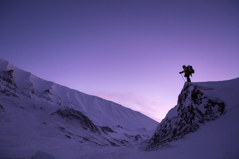A climber looks across the Canadian landscape as the sun sets.