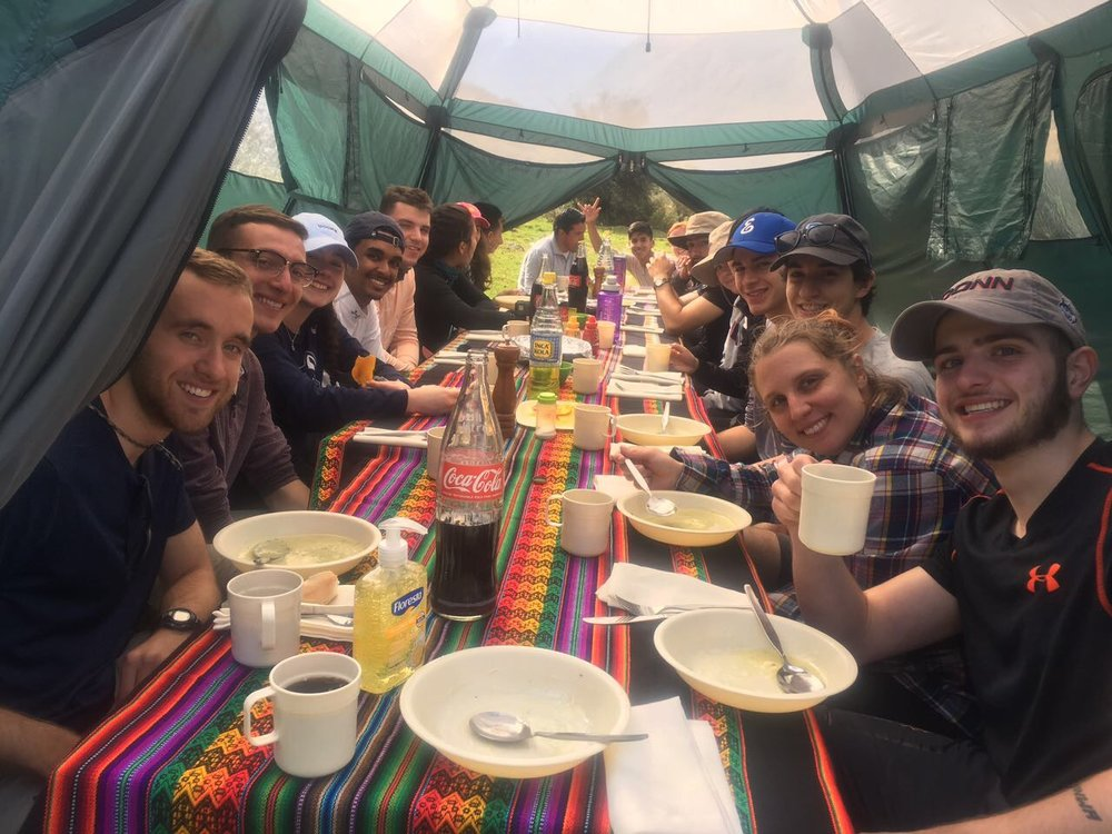 College students enjoying a meal while trekking to Machu Picchu