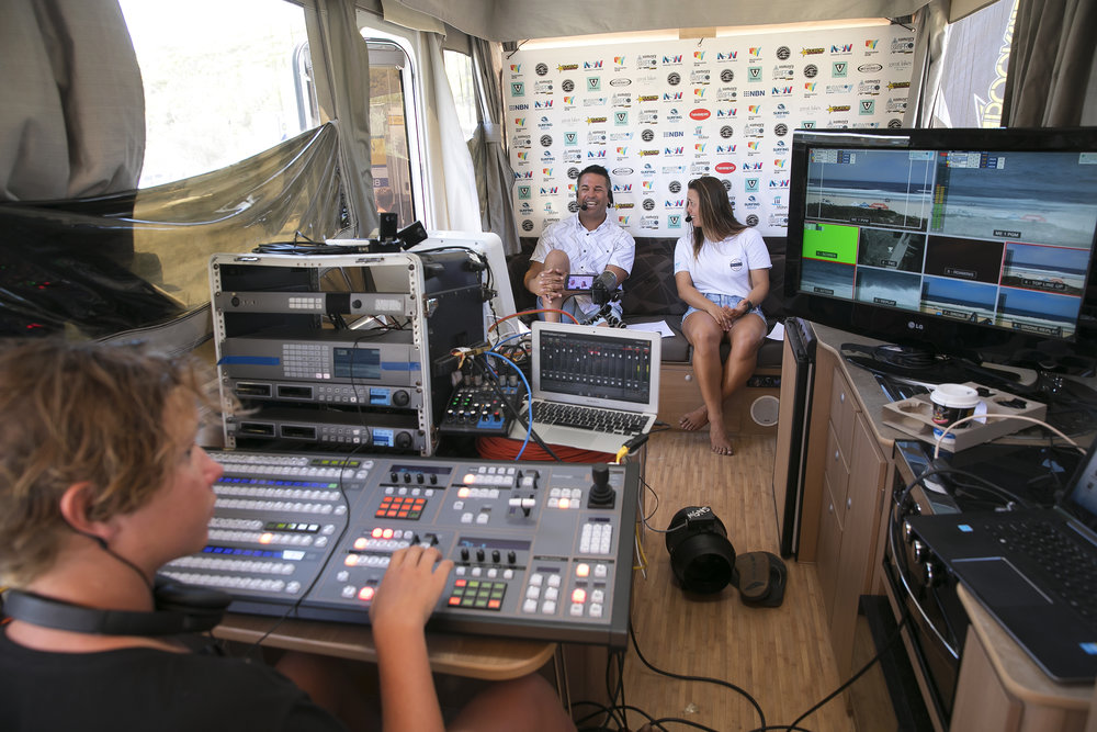 John Shimooka (centre) commentating in a trailer studio at Boomerang beach.
