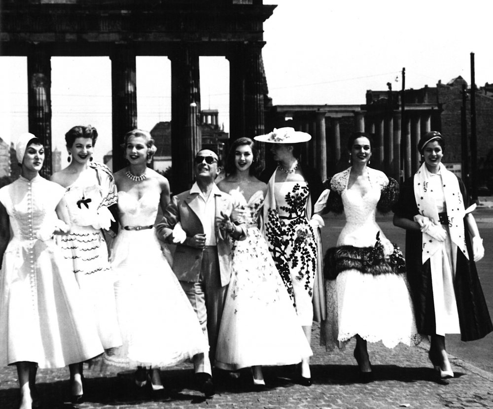 Pictured with models in his designs, 1953