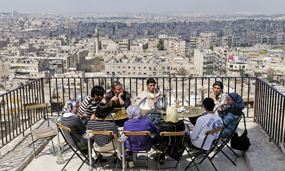 "Aleppo, Syria in 2009. ""Young people socialising (sic) on the hill of the Citadel of Aleppo, two years before the start of the Arab spring protests that led the civil war."" via The Guardian Photograph: imageBROKER/REX/Shutterstock"