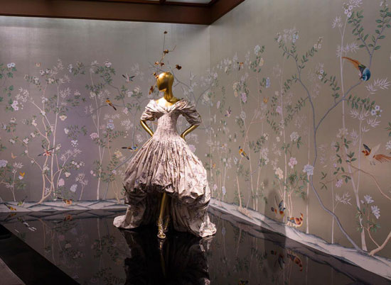 An image from 2015 exhibition China Through the Looking Glass at The Metropolitan Museum of Art. Dress: Alexander McQueen AW2006; wallpaper: de Gournay chinoiserie. Image via de Gournay.