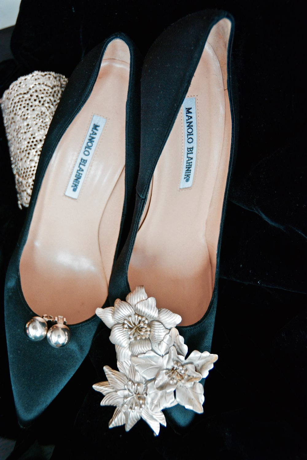 A pair of clip-on earrings adorns one shoe, while a silver brooch adorns the other.