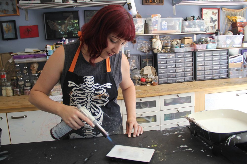 Shannon Amidon using a torch to fuse and encaustic piece