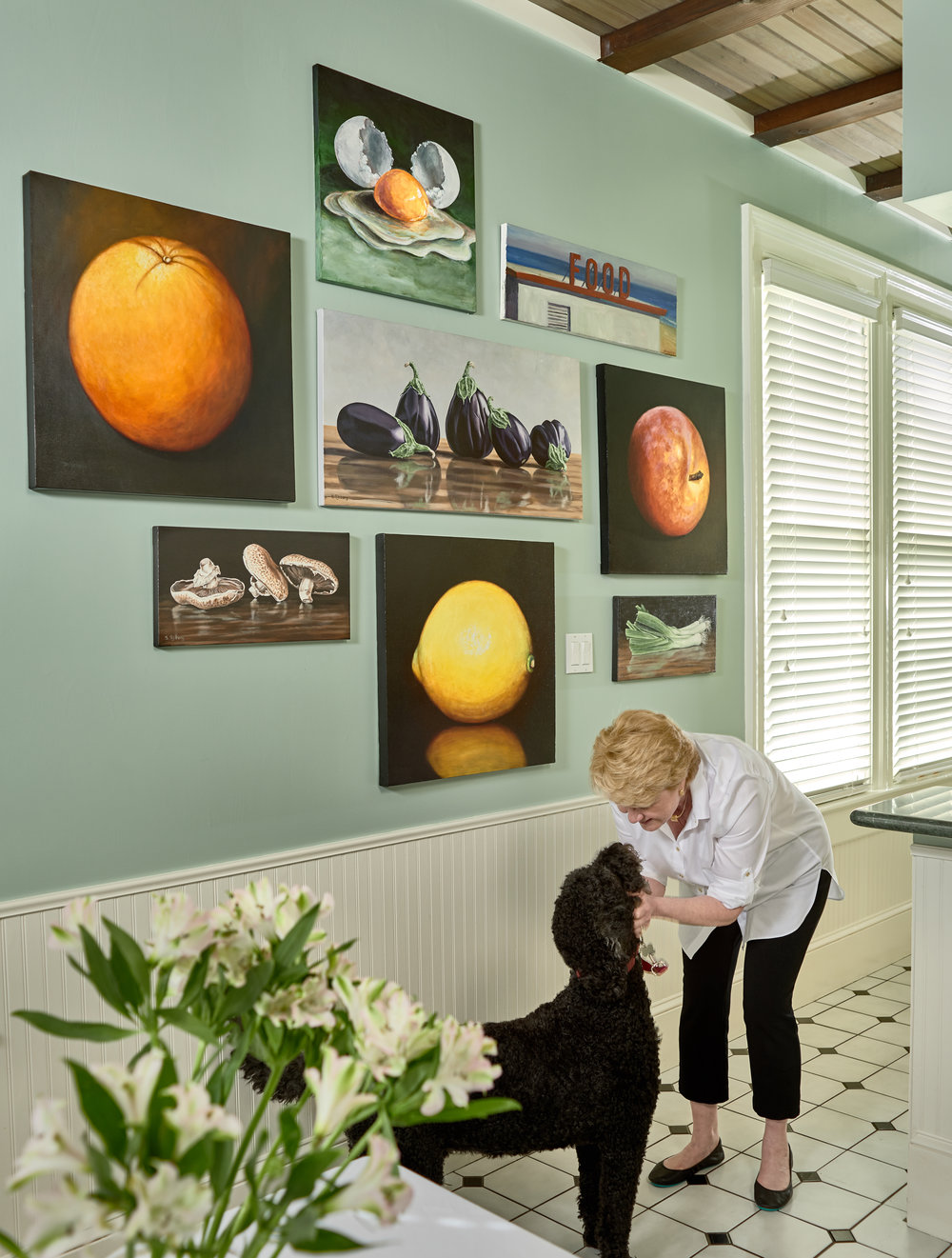 C.H. and her dog in front of a culinary-themed gallery wall including artwork by UGallery artists Kristine Kainer, Susan Sjoberg, Tami Cardnella, and John Kilduff.